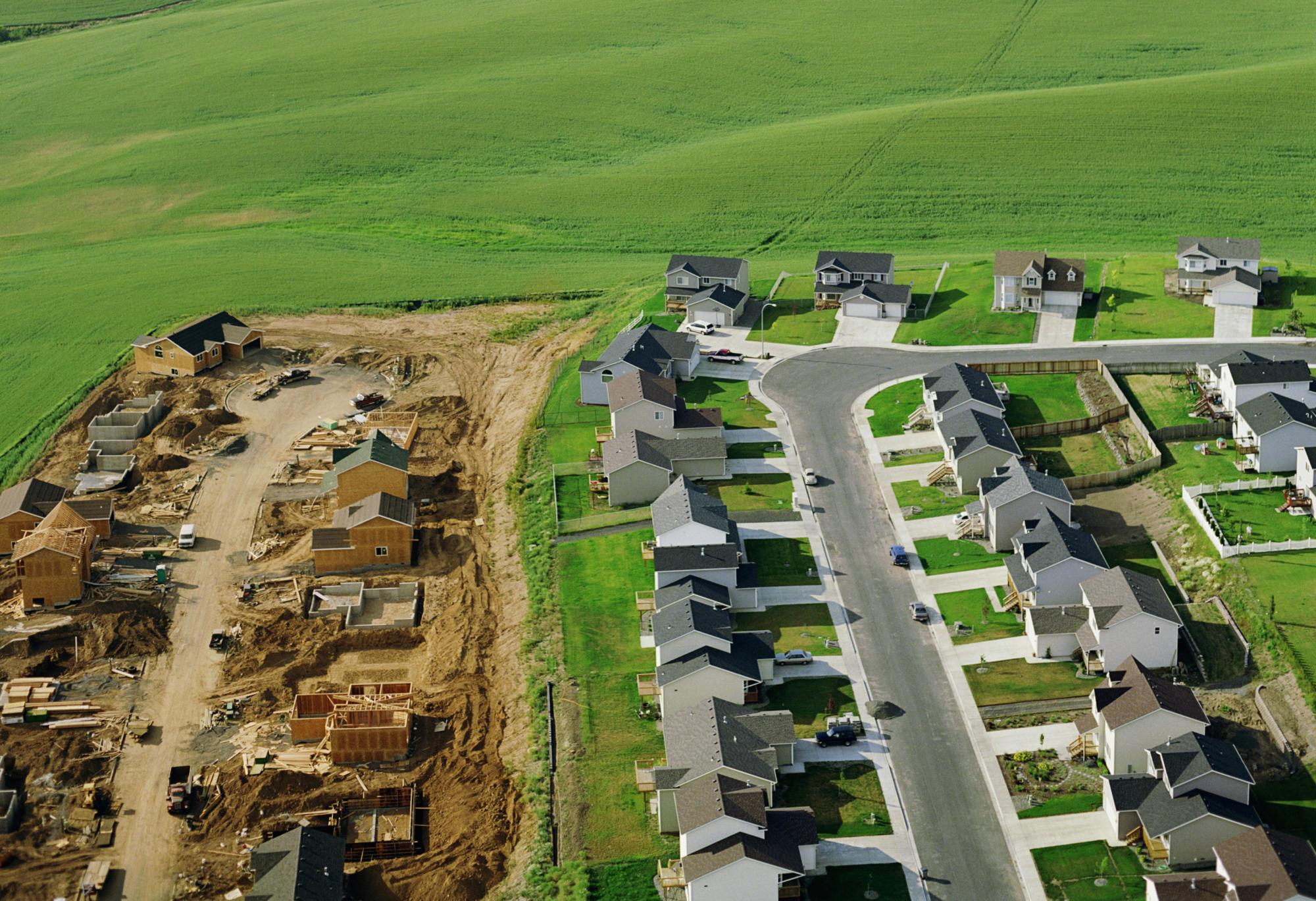 Housing development under construction on farmalnd, aerial view.